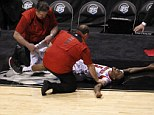 Horrific: Kevin Ware, 20, screams with pain as trainers cover his leg following a crippling injury Sunday night during the Louiseville-Duke game