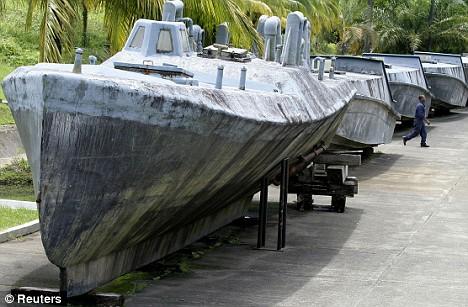 Makeshift: A man walks between a makeshift fiberglass submarine  and speedboats