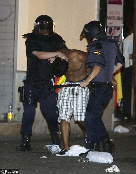 Your nicked: Riot police arrest a soccer fan during riots after the Euro 2008 final