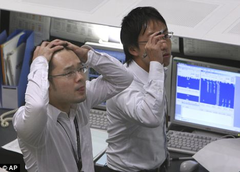 Disbelief: Traders in Japan struggle to believe their eyes as stocks plunged 9.6 per cent today