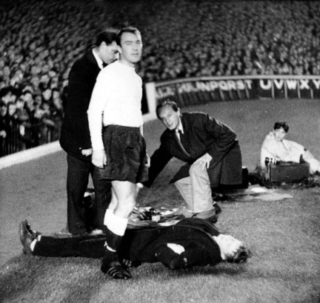Jimmy Greaves goes to help a boy that lies flat out after being hit in the face by the ball  (Photo by Bentley Archive/Popperfoto/Getty Images)