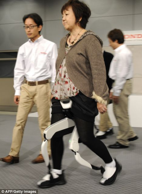 A female journalist tries Japan's auto giant Honda Motor walking assist device with bodyweight support system at the company's headquarters in Tokyo