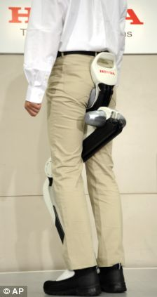 A researcher shows off Honda Motor Co.'s experimental walking assist device with bodyweight support system