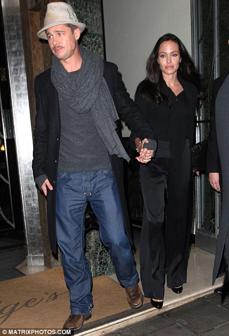 Showing the strain: Brad Pitt and Angelina Jolie leave the Claridge's hotel on their way to the press conference