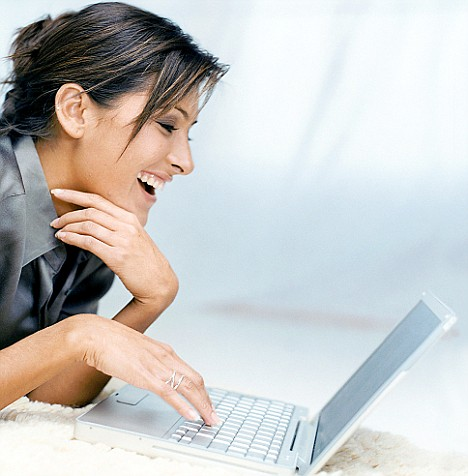 Woman with laptop laughing.Online shopping...