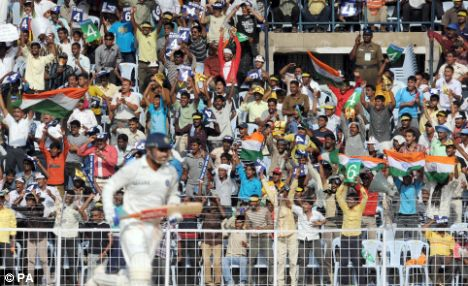 ian fans celebrate as Virender Sehwag hits a boundary during the fourth day of the First Test Match at the M. A. C