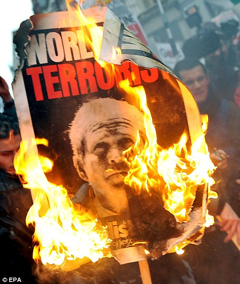 Burning bush: A placard bearing a portrait of U.S. President George Bush is set alight. There were reports of rioters trying to set police vans alight