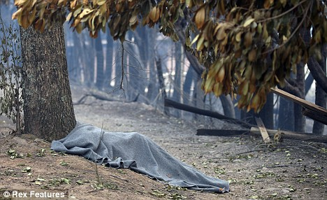 Hell on earth: A body lies at the side of the road in Marysville as Australia is devastated by fire