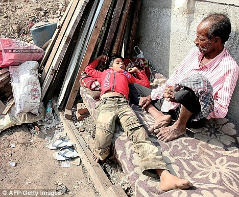 Living in squalor: Amid rat-infested rubble, the ten-year-old and his father Mohammed rest on a cot outside their shanty