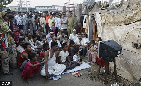 Neighbours of actor Azharuddin Mohammed Ismail (Jamal) watch the Academy Awards near his home, in a slum in Bandra, Mumbai, India