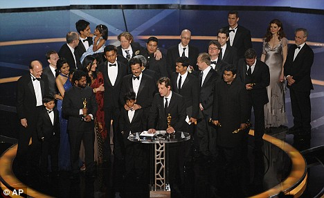 Producer Christian Colson is joined by the cast and crew of Slumdog Millionaire onstage after the film is named Best Picture