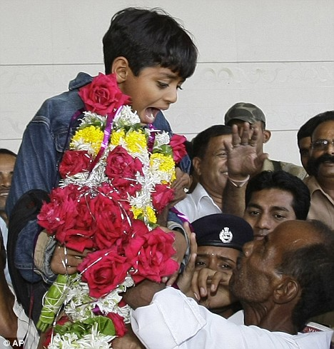 Azharuddin Ismail is lifted up by his father  Mohammed as he arrives at Mumbai airport after the Oscars