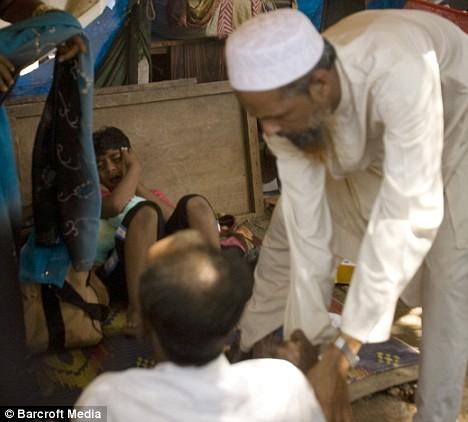 Neighbours restrain Mohammed Ismail, below, as his son Azharuddin cries