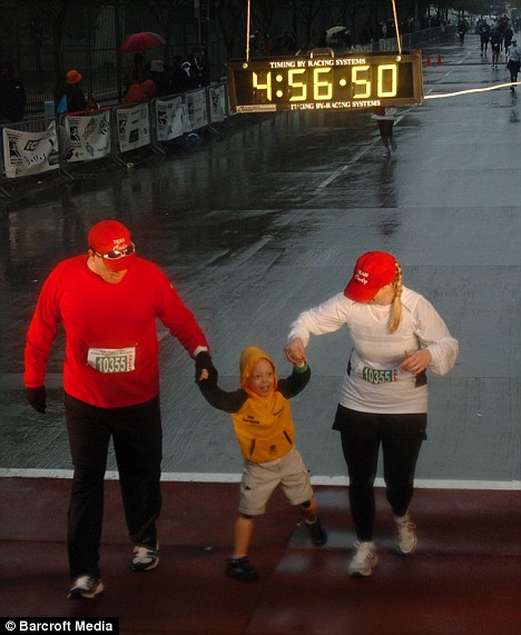 Cody's face is joyful as, clutching hands with mumTina McCasland and dad Mike McCasland he crosses the line at the Dallas White Rock Marathon