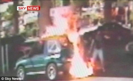 The explosion engulfs the vehicle as the driver backs away
