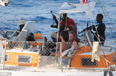 Hostages are held at gunpoint by pirates aboard the Tanit