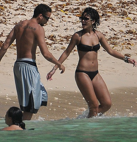 Chris who? Rihanna splashes about on Sandy Lane beach in Barbados with mystery man