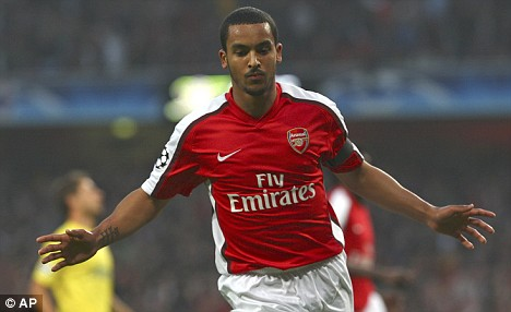 Red alert: Walcott in Arsenal's home kit, which the Gunners will continue to wear until the end of next season