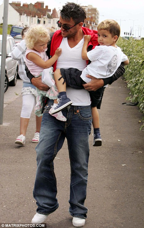 Doting daddy: Peter carries his youngsters during their day out