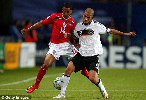 Stalemate: Substitute Theo Walcott is stopped in his tracks by Germany's Ashkan Dejagah during the 1-1 draw