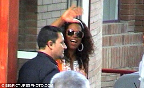 Hi there! Oprah waves to the watching paparazzi