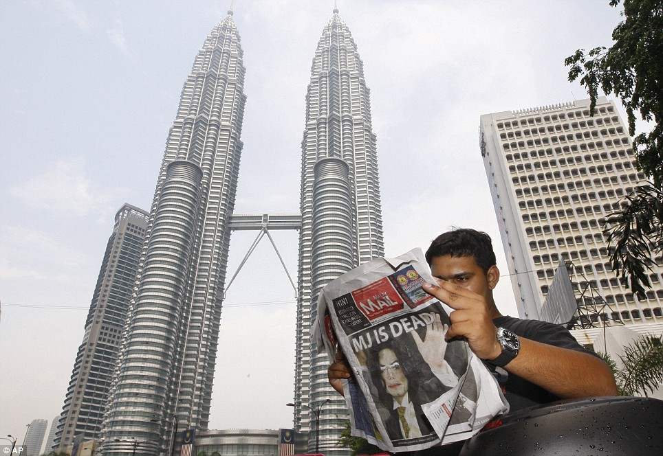 A motorcycle courier reads an afternoon paper in Kuala Lumpur, Malaysia, with the announcement that US rock legend Michael Jackson