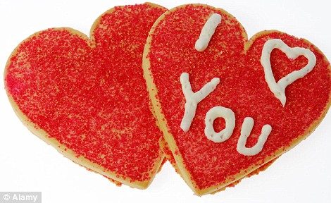 A7BMNX Two red heart shaped cookies with I love you