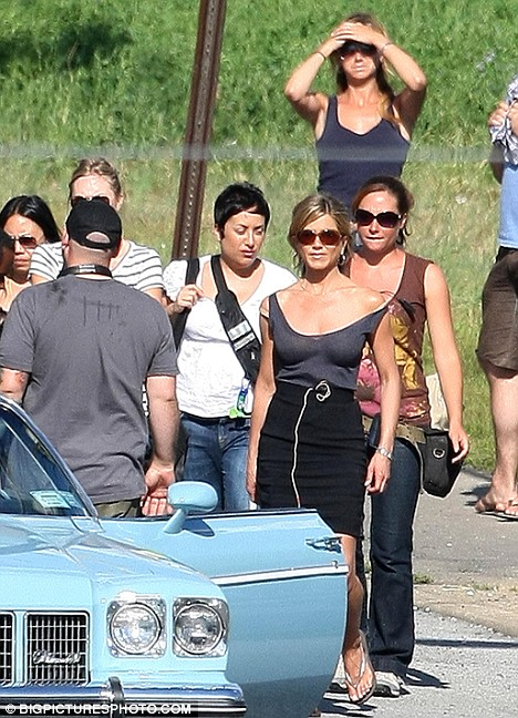 Back to work: Jennifer prepares for her scene on-set, while a body double waits in the background