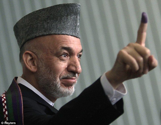 Afghan President Hamid Karzai holds up his ink-stained finger after voting in the presidential election in Kabul today