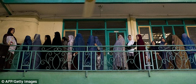 Afghan women stand in line as they wait for the opening of a polling centre in Kabul this morning, defying the Taliban's orders not to vote