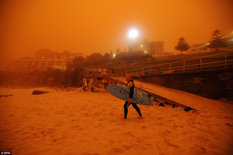 Red sea: A surfer heads for the water as a dust storm blankets Sydney's iconic Bondi Beach