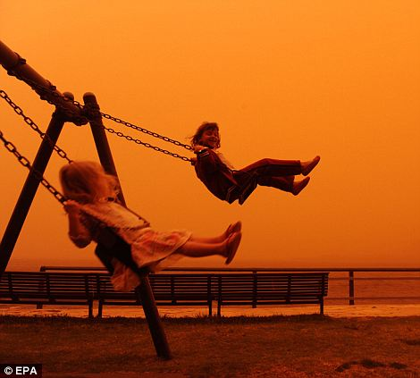 Glowing joy: Six-year-old Ariella and her three-year-old sister Romy enjoy an early morning swing amid a dust storm in the Balmain area of the city