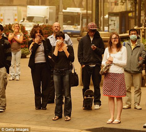 Fear: Residents of Sydney cover their mouths as health authorities warned the dust could cause serious breathing problems
