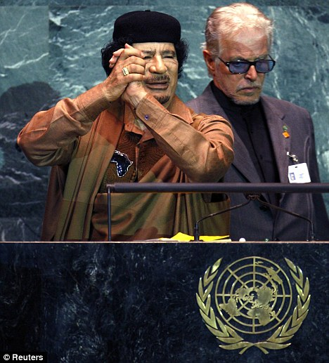 Muammar Gaddafi gestures at the end of his speech as an aide gathers his notes, during the 64th United Nations General Assembly at the U.N. headquarters in New York