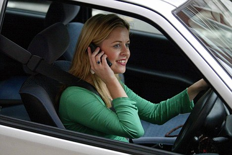 Drivers who talk on their mobile phones at the wheel, like this woman (stock photo), are the number one pet hate for motorists