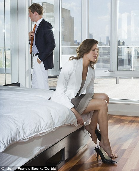 A woman gets dressed while sitting on bed. Man looks away out of window