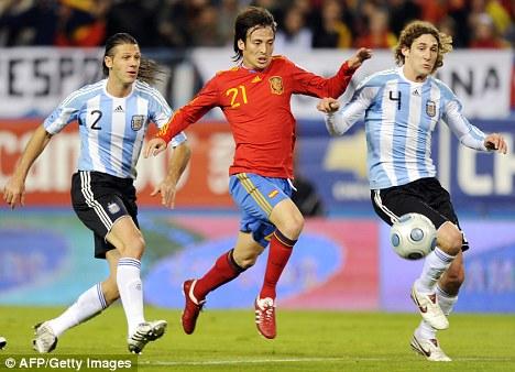 Spain midfielder David Silva (centre) with Argentina's Fabricio  Coloccini (right) and Martin Demichelis