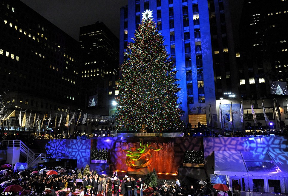 The White House trees weren't the only famous trees lit in America yesterday: Here the lights of the 77th Annual Rockefeller Center Christmas Tree are switched on at a ceremony in New York last night