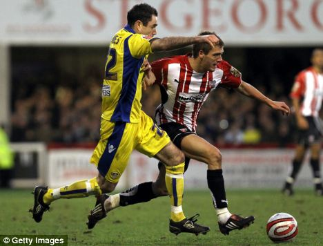 Ryan Dickson (right) of Brentford is challenged by Andrew Hughes of Leeds United