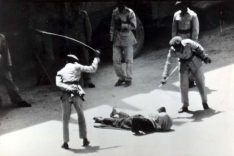A criminal gets a public flogging by two officials in Saudi Arabia