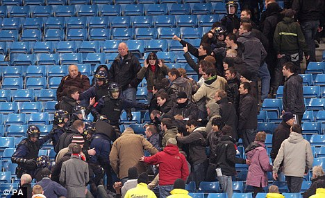 Police attempt to control fans after the final whistle during the Carling Cup Semi Final