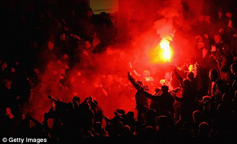 Manchester United fans let off a flare during the Carling Cup Semi Final