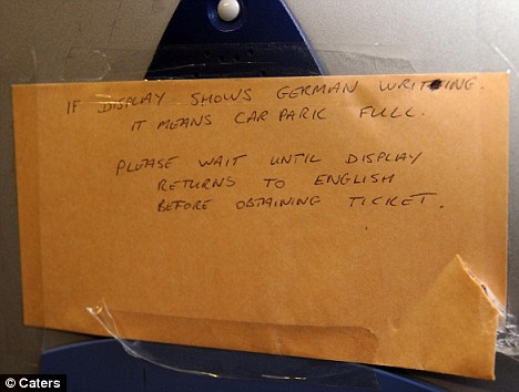 A sign attached to the ticket machine tells motorists to wait until the display returns to English before entering