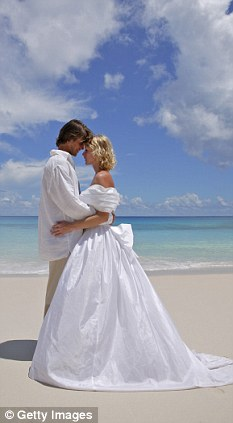 Bride and groom embracing on beach posed by models