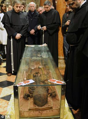 Monks look at the skeleton of St Anthony in the Relics Chapel of Padua's Basilica, Italy