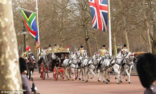 A carriage carrying Queen Elizabeth II and South African President Jacob Zuma processes along The Mall
