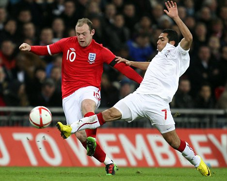 Wayne Rooney of England holds off Ahmed Fathy of Egypt