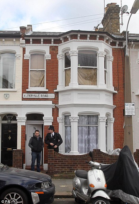 Grim discovery: Police stand guard in front of the house, where a body was unearthed last night