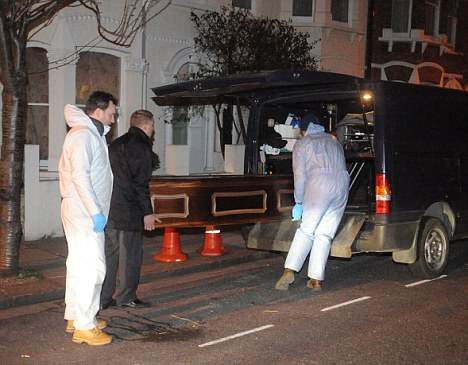'Buried for up to 20 years': Police remove the body from the property last night