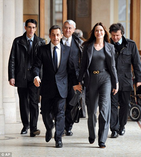 Sarkozy and his wife walk to the polling station. Rumours surfaced last week that they are both having affairs